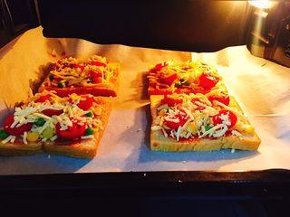 快手吐司披萨,吐司披萨放入烤箱的中层,上下火180度,烤15分钟左右,奶酪融化即可。