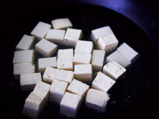 肉末青蒜烩豆腐,北豆腐洗净后用刀切成小块,锅中倒入适量的清水烧开后,加入一勺盐放入豆腐进行焯水后捞出沥干水分备用。