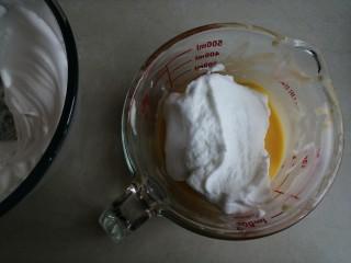 香草舒芙蕾,蛋清用电动打蛋器打至粗泡时,分两次加入剩余的细砂糖,打发至干性发泡的蛋白霜。取1/3打发好的蛋白霜打蛋黄糊里,从底部向上翻拌并切拌均匀
