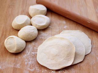 蘑菇海虹麦穗包,把剂子摁扁后,用擀面杖擀成圆形薄面皮。
