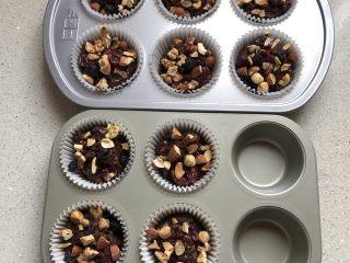巧克力果仁小蛋糕,将蛋糕糊装入纸杯,上面撒入果仁,最好按紧一点。