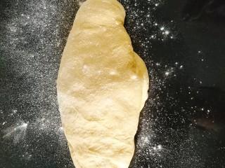 南瓜泥奶香吐司,发酵好的面团取出放在大理石操作台上轻撒一层干面粉防止粘手,用手轻压给面团排气,或者用擀面杖擀一下;