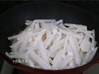 客家风味杂菜煲,倒进萝卜条翻炒十几个来回。
