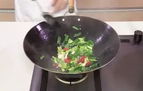 回锅羊肉片,倒入蒜苗、青椒、红椒,快速翻炒至断生。