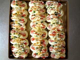 花式芝士肠仔包,发酵完成取出表面喷水放入芝士碎,香葱碎,挤上沙拉酱和番茄酱