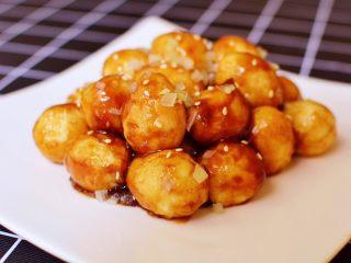 糖醋虎皮鹌鹑蛋,表面撒上熟白芝麻和葱花点缀。