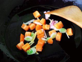 茼蒿肉末营养羹,锅烧热后,先爆香葱姜再放入胡萝卜丁翻炒片刻。