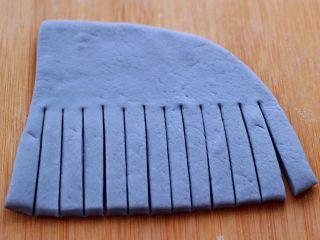 蝶豆花火腿肠花卷,取其中一个面片,用刀从中间切成1厘米宽的条状。