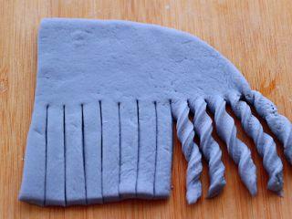蝶豆花火腿肠花卷,然后用手把切好的条条扭上4、5下,形成麻花状。