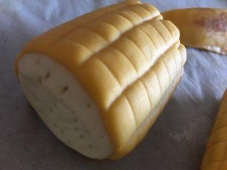 玉米馒头,裁出长宽合适的尺寸,沾点水包裹在白色小面段上,收口朝下放,用牙签在侧面白面团扎几下