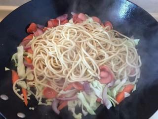 卷心菜香肠炒面,把把煮好的面条放入锅中和蔬菜一起煸炒。