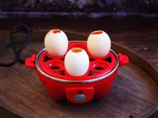 琥珀鸡蛋,将剪好小洞洞且倒出去一点点蛋清的鸡蛋妥妥的放在快速煮蛋器的搁架子上。