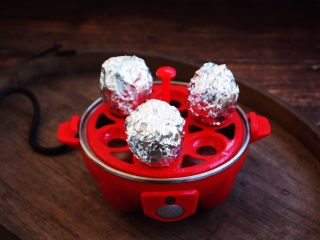 琥珀鸡蛋,用锡纸将鸡蛋包裹好,放在快速蒸蛋器的搁架上。