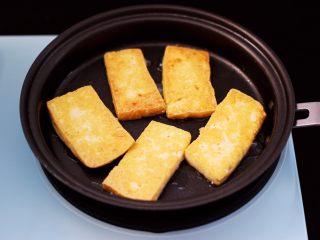 香辣煎豆腐,中小档将豆腐煎至金黄,再翻一面,两面都煎至成金黄色。