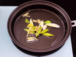 辣爆猪肝,早餐机的煎锅里倒入花生油烧热后,先爆香蒜苗和姜丝。