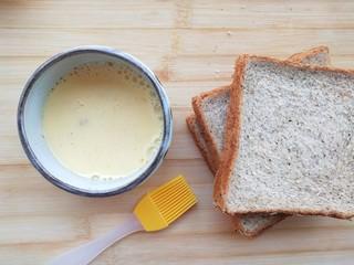 太阳刚出山头,我做了这份芒果西多士给你,取小刷子,将吐司刷上混合液。   放入烤箱5分钟。   将芒果切丁备用。