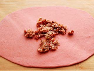 蒜香粉嫩肉龙花卷,把搅拌好的肉馅倒入面皮上。