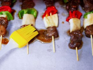 时蔬美味牛肉串,烤至15分钟后取出烤盘,将肉串两面刷上橄榄油,再撒上孜然粉,再次送入烤箱烤10分钟。