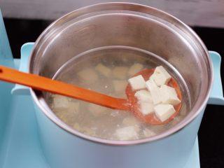 虾皮翡翠白玉羹,东菱早餐机的汤锅里,加入适量的清水烧热后,放入豆腐焯水后,捞出沥干水分备用。