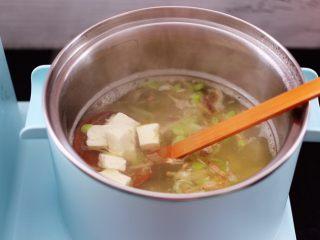 虾皮翡翠白玉羹,大火煮沸后,把焯水的豆腐放入锅中。