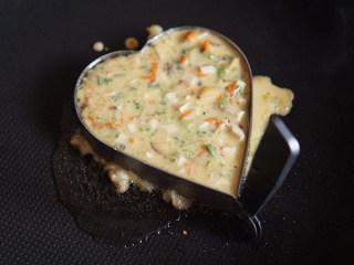 爱心鸡蛋饼,等油温度稍高之后,倒入搅拌好的材料,中火凝固