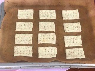 芝麻奶香苏打饼干,摆在烤盘上,用叉子扎眼,这时开始预热烤箱。