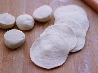 小苔菜虾皮花样包子,把剂子摁扁后,用擀面杖擀成圆形薄面皮。