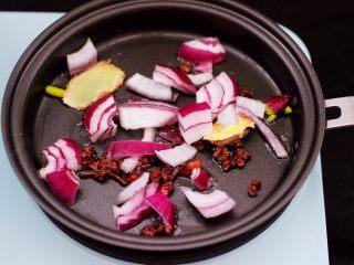 番茄牛肉炖土豆,煎锅里倒入花生油烧热后,先小火慢慢炸香花椒和八角,再爆香洋葱。