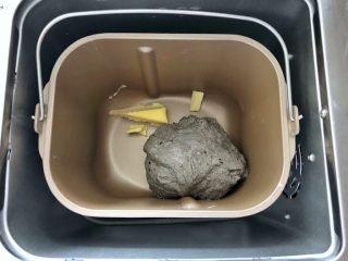 黑芝麻吐司(一次发酵),启动面包机的揉面程序,把干酵母揉进面团里即可停止揉面,接下来放入黄油。