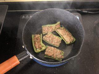 香辣可口的青椒酿肉,小锅内倒入适量的油烧热,码放好青椒酿肉小火两面煎一下。