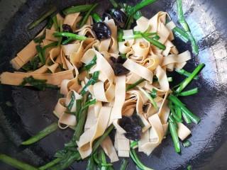 韭香豆腐皮,根据个人口味再加入适量的盐和鸡精,大火翻炒均匀,韭菜断生即可出锅。