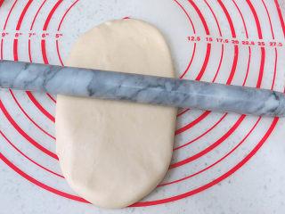 冷藏中种法滴【淡奶油吐司】,取一个松弛好的面团,光面朝下擀成椭圆