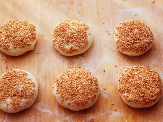 果仁红糖发面饼,用手摁扁后,白芝麻放到一个盘子里,把饼蘸上白芝麻。