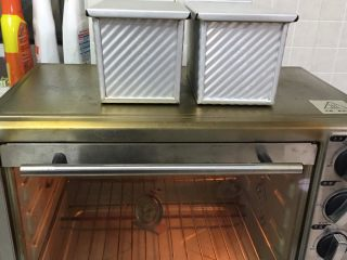 奶酪双吐司,烤箱预热至190度,吐司盒送入烤箱。