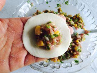 芹菜玉米猪肉馅饺子,取一饺子皮放在手上放入适量的馅