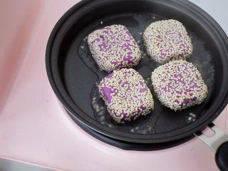 奶香紫薯饼,平底锅烧热,再放入紫薯饼,两面先煎至定型,再撒上1勺水,盖上锅盖煎至水干