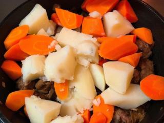 马铃薯炖肉,洋葱炒完后 依序放入牛腩、马铃薯、红萝卜!全部拌炒在一起,同时也把酱汁準备好,比例是1:2喔 酱汁準备好了、食材也拌炒均匀了,就把酱汁倒入锅中吧!要让酱汁盖过食材喔
