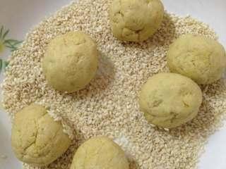 红薯糯米饼,放入芝麻中滚圆沾满芝麻,要用生芝麻,以免炸的时候糊了