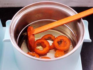 鹅蛋时蔬炒意面,汤锅里加入适量清水煮沸后,加入适量的盐,把胡萝卜进行焯水。