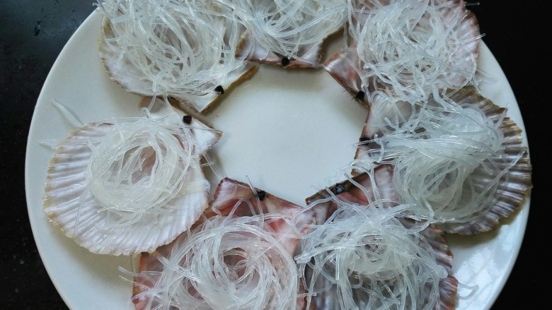 蒜蓉粉丝蒸扇贝,将泡好的粉丝码放在扇贝壳上