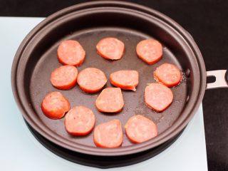 对虾红肠时蔬泡面,用煎蛋的锅,直接把切片的红肠放入煎锅中。