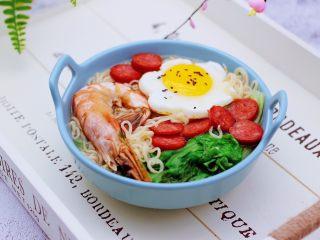 对虾红肠时蔬泡面,把煮好的方便面盛到碗里,上面码放好煎过的鸡蛋和红肠,就可以开始享用了。