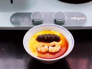 海参虾仁鸡蛋羹,把煎好的虾仁和海参码放到碗里,浇上生抽就可以咯。