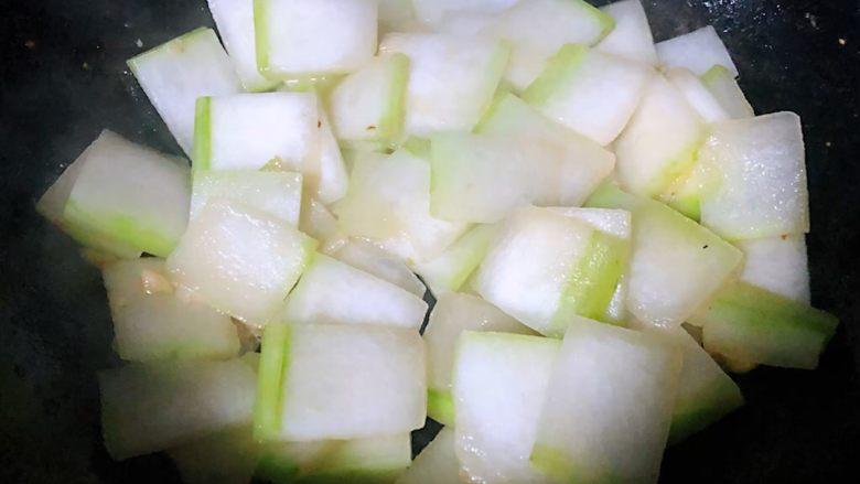 虾滑冬瓜针菇汤,锅中倒入底油加热放入葱、蒜爆香再放入冬瓜片翻炒