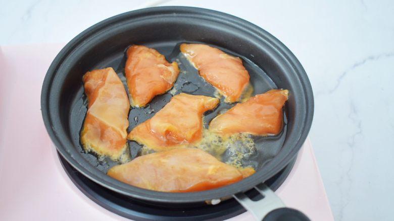 蜜汁鸡胸肉,平底锅刷一遍食用油烧至7-8成热,放入腌制好的鸡胸肉