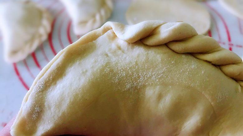 韭菜盒子,面饼的一侧对折,捏紧封口,如图,捏出花纹。