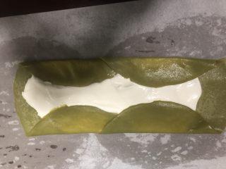 抹茶毛巾卷,取两张饼皮半叠铺好,加入打发好的奶油,抹平,按如图所示把两边向中间折好。