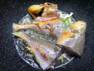 酸菜炖黄鱼,煎好一面翻另一面继续煎制,待两面煎好以后,放入葱白爆香。