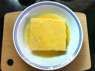 芒果酸奶土司,把夹入水果的吐司放入鸡蛋液中,上下和四周都均匀地裹上一层蛋液.