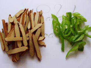 凉拌紫甘蓝香干,香干也用刀切成薄片,青尖椒用刀切成丝备用。